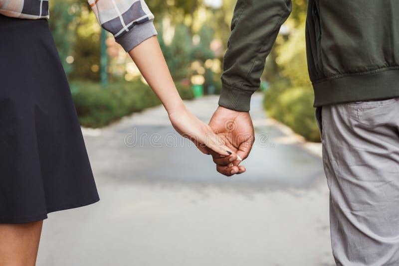 Le coppie multietniche nell'amore camminano in primo piano del parco immagini stock libere da diritti