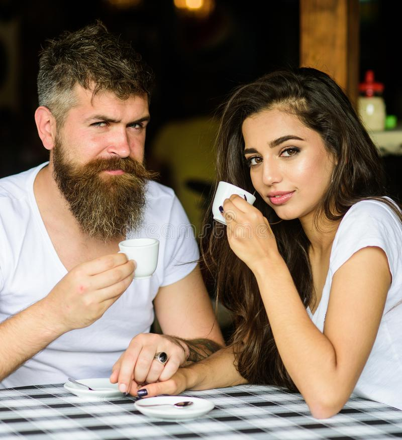 Le coppie nell'amore bevono il caffè nero del caffè espresso in caffè L'uomo con la barba e la ragazza sorridente felice attraent immagine stock