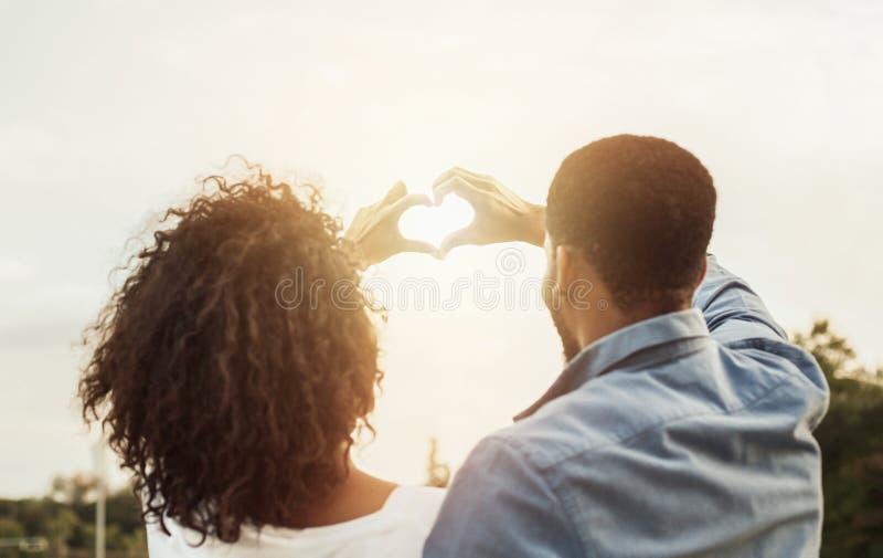 Le coppie nell'amore che fa il cuore modellano con le mani fotografie stock