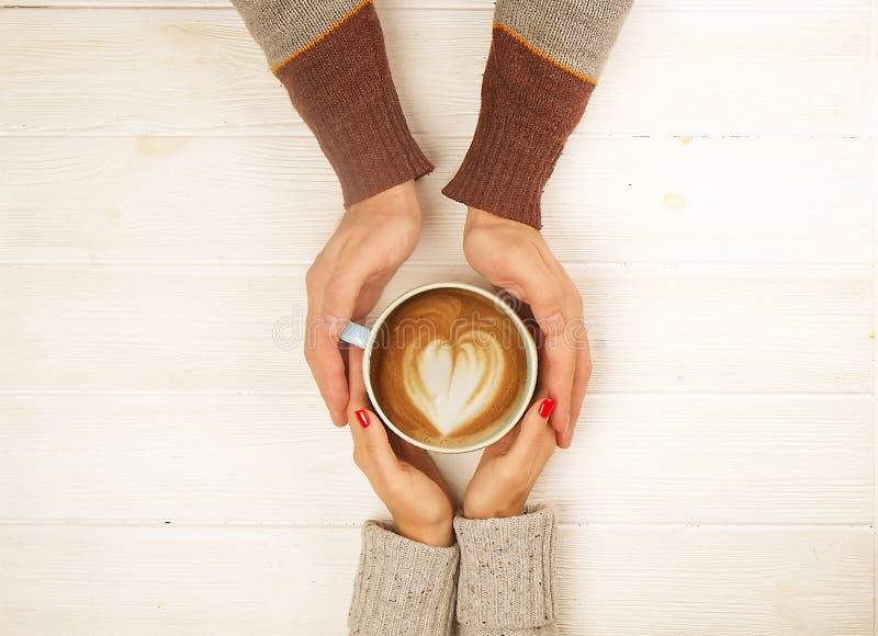 Le coppie nell'amore che tiene la tazza di coffe in mani sulla vista superiore del fondo di legno, annata hanno tonificato l'imma fotografia stock libera da diritti