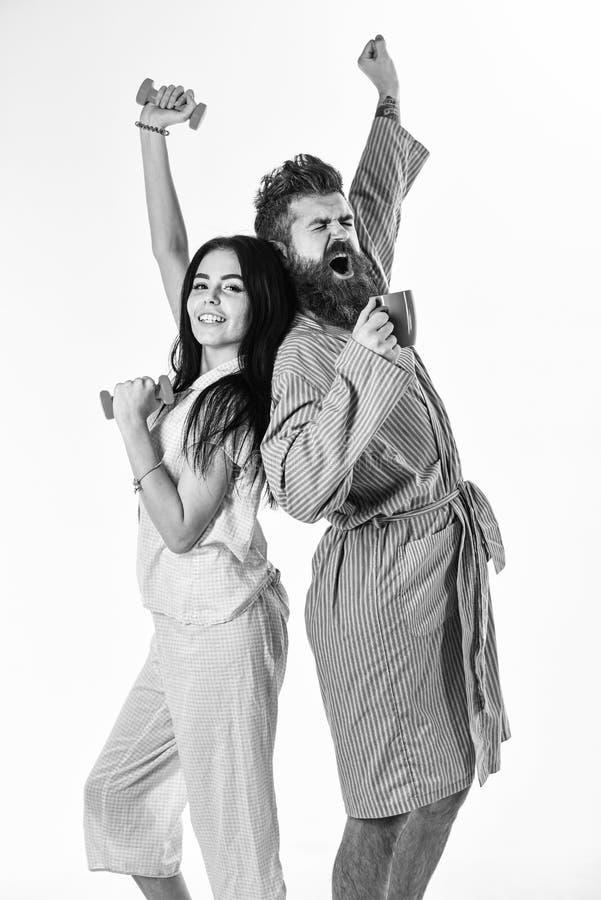 Le coppie nell'amore in pigiama, accappatoio stanno indietro per appoggiare Concetto di energia di mattina Ragazza con la testa d fotografia stock