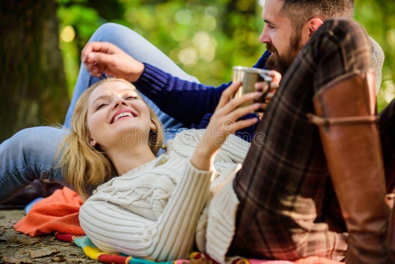 Le coppie nell'amore si rilassano nella foresta di autunno con tè o caffè donna felice e vin brulé barbuto della bevanda dell'uom immagini stock libere da diritti