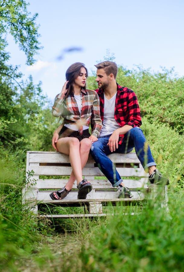 Le coppie nell'amore si siedono sul banco Ragazzo ed amica nell'amore Concetto di romance e di amore va in bicicletta il fine set immagini stock