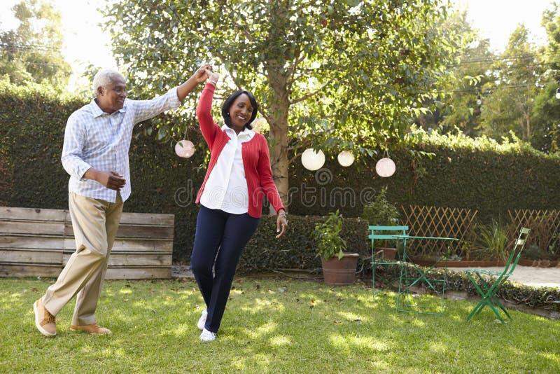 Le coppie nere senior ballano nel loro giardino posteriore, integrale fotografie stock libere da diritti
