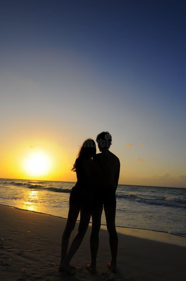 Le coppie proiettano sull'oceano di tramonto immagini stock libere da diritti