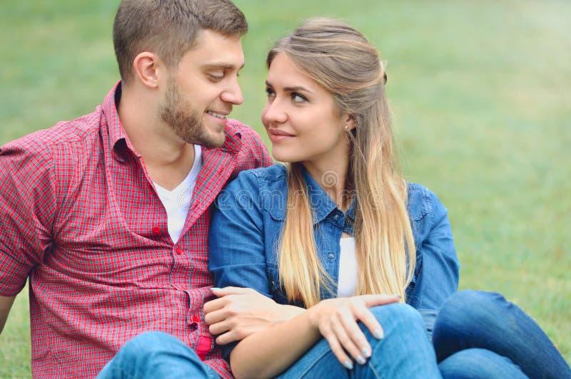Le coppie romantiche che si siedono sull'erba e si esaminano occhi del ` s fotografie stock libere da diritti