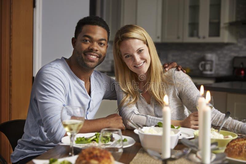 Le coppie romantiche della corsa mista osservano alla macchina fotografica il pasto in cucina fotografie stock