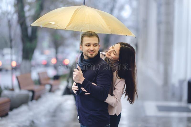 Le coppie romantiche felici, il tipo e la sua amica vestiti in abbigliamento casual stanno abbracciando sotto l'ombrello ed esami fotografia stock libera da diritti