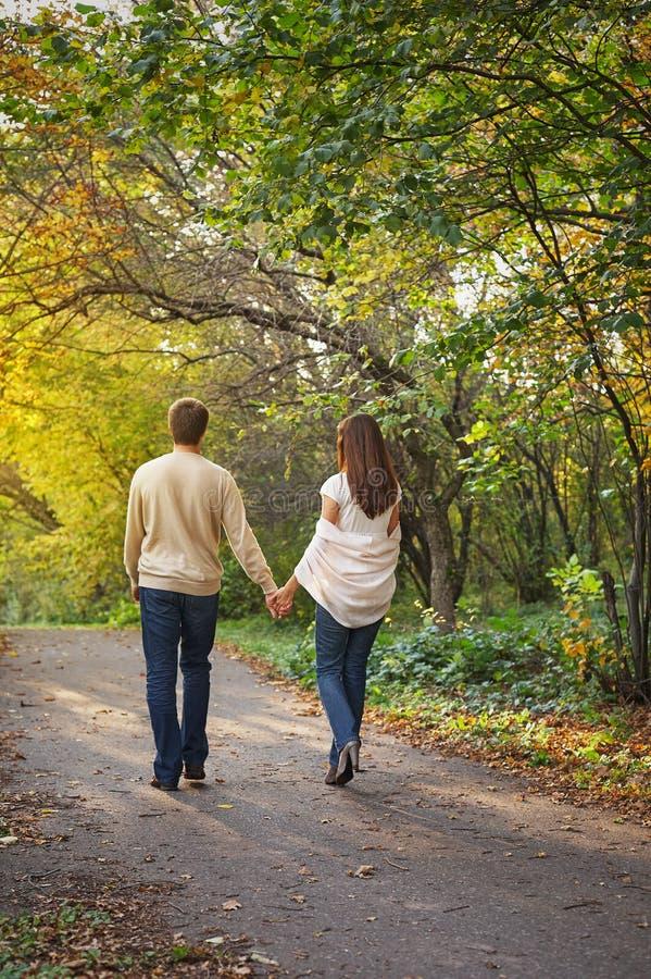 Le coppie romantiche giovani nell'amore che cammina in autunno parcheggiano tenersi per mano fotografia stock libera da diritti