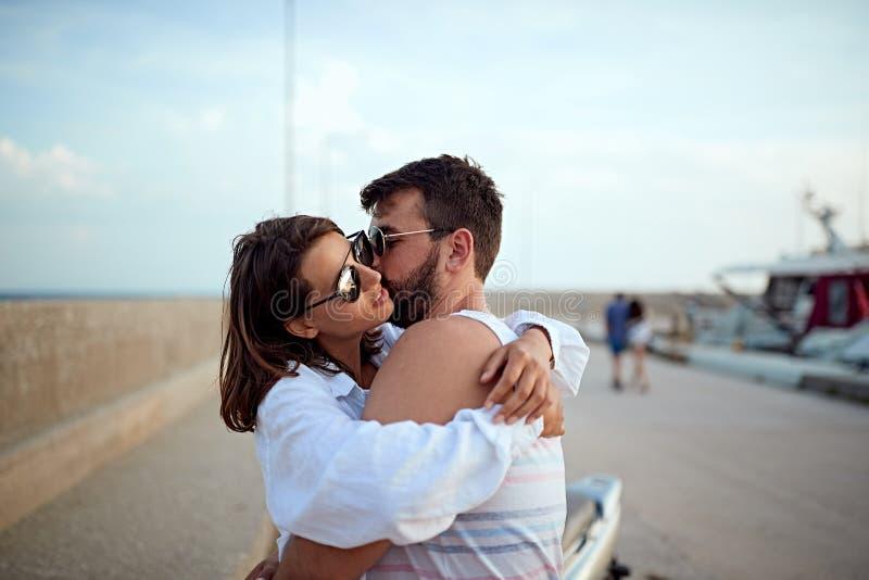 Le coppie romantiche hanno abbracciato vicino agli yacht sul bacino immagini stock