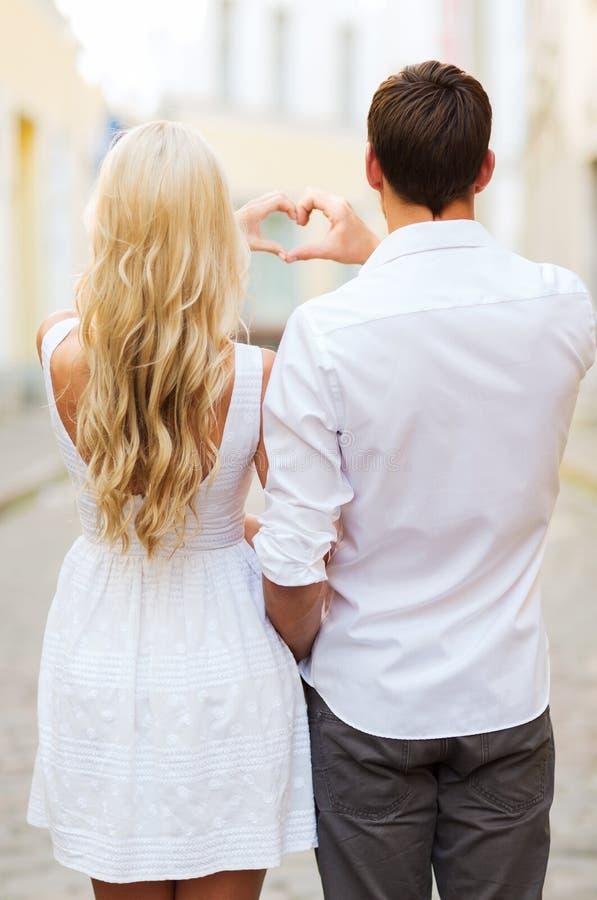 Le coppie romantiche nella città che fa il cuore modellano immagine stock