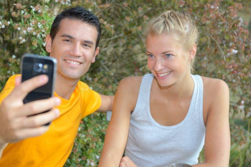 Le coppie romantiche prendono la foto del selfie durante l'aumento in natura fotografie stock