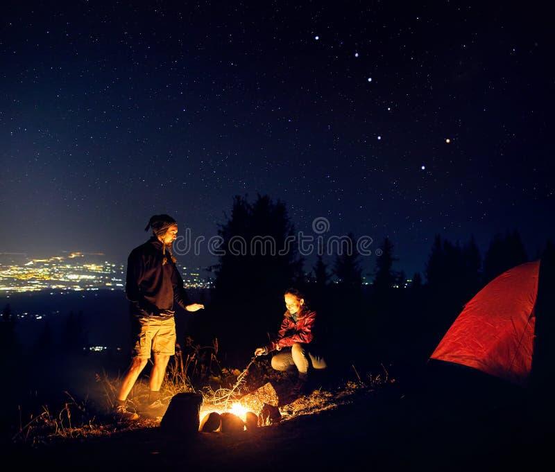 Le coppie romantiche si avvicinano al fuoco di accampamento alla notte stellata immagini stock
