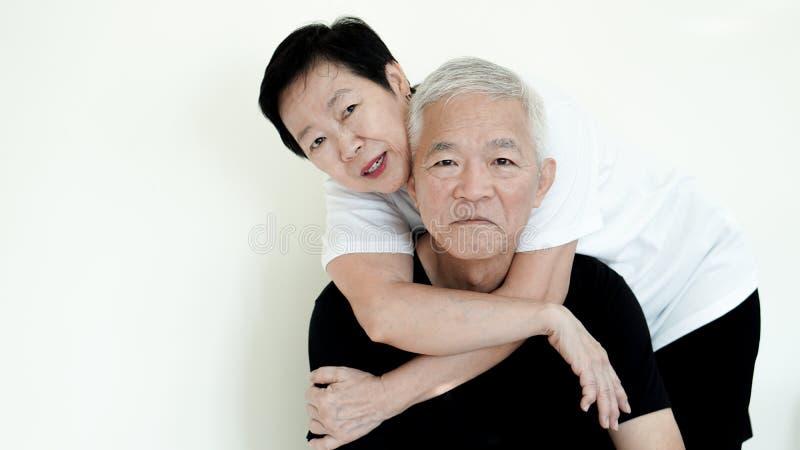 Le coppie senior asiatiche sorridono, vita senza la preoccupazione su backgroun bianco immagine stock