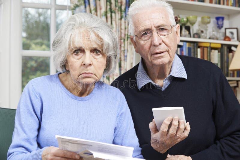 Le coppie senior a casa con le fatture si sono preoccupate per le finanze domestiche fotografie stock libere da diritti