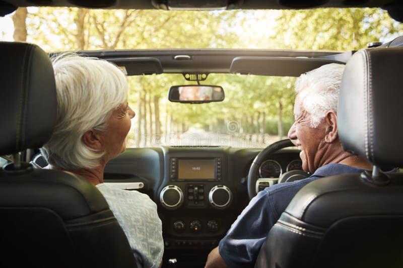 Le coppie senior conducono l'automobile senza coperchio sul viaggio stradale della campagna fotografie stock