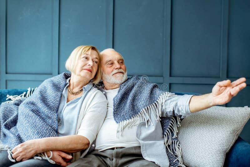 Le coppie senior di Lovele si sono avvolte con il plaid a casa fotografia stock libera da diritti