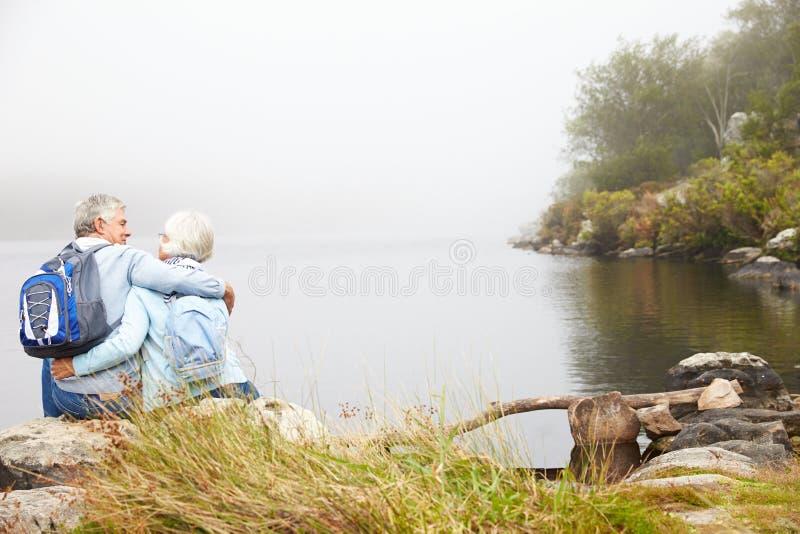 Le coppie senior si siedono l'abbraccio da un lago, vista posteriore immagine stock