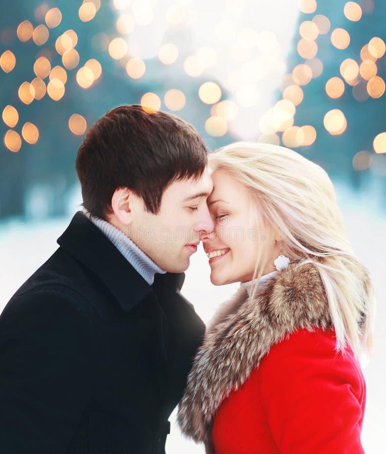 Le coppie sensuali romantiche di Natale nell'amore all'inverno freddo sopra il bokeh della celebrazione, addolciscono il momento  fotografie stock