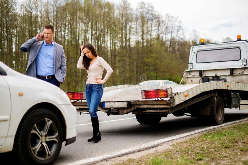 Le coppie si avvicinano all'automobile rotta su un bordo della strada immagini stock libere da diritti