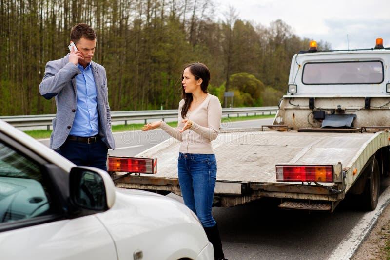 Le coppie si avvicinano all'automobile rotta su un bordo della strada immagini stock