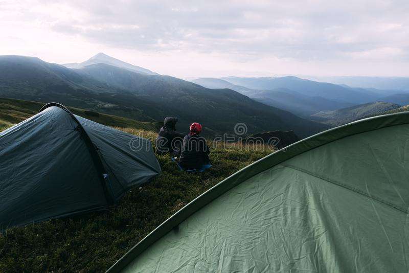 Le coppie si avvicinano alla tenda sul primo piano delle montagne fotografia stock