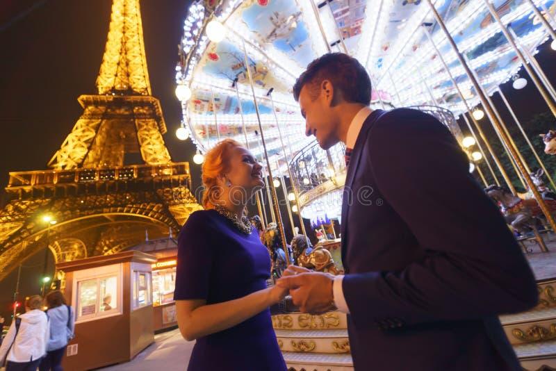 Le coppie si avvicinano alla torre Eiffel alla notte immagini stock libere da diritti