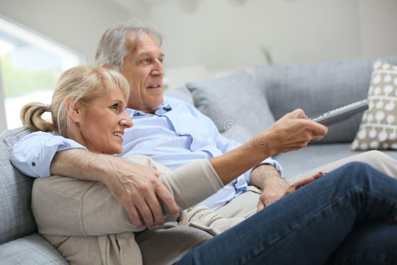 le coppie si dirigono la sorveglianza maggiore della TV immagine stock