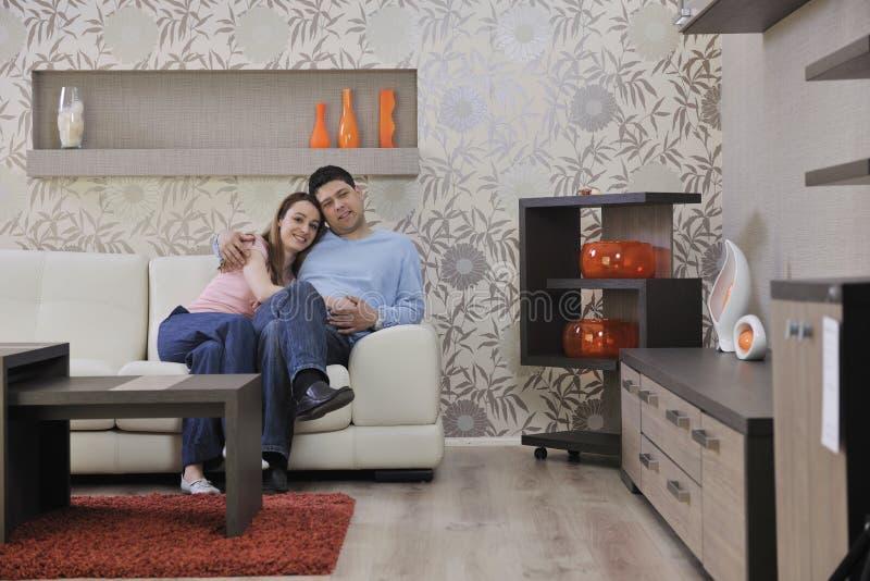 Le coppie si distendono nel paese sul sofà in salone fotografie stock libere da diritti