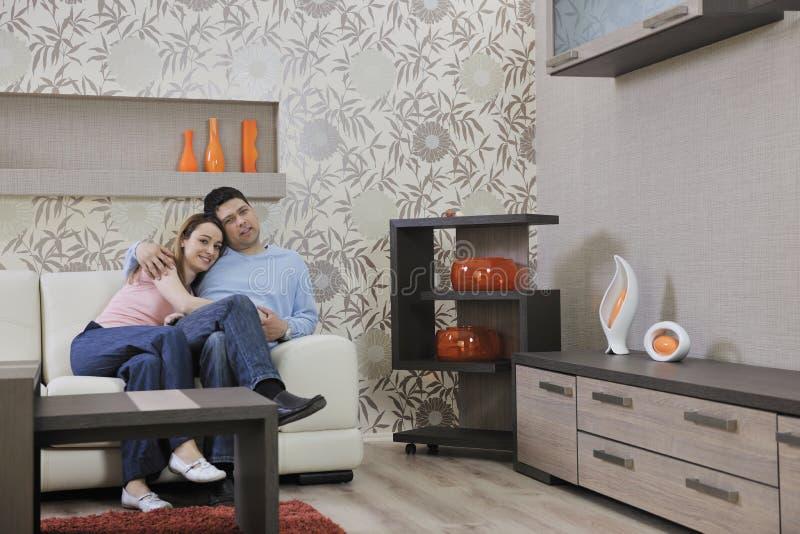 Le coppie si distendono nel paese sul sofà in salone immagine stock