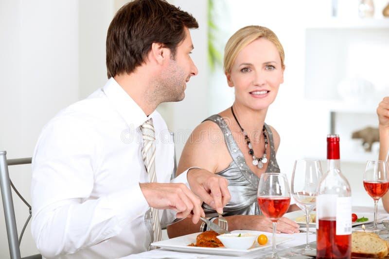 Le coppie si sono sedute alla tabella che mangia il pasto fotografia stock