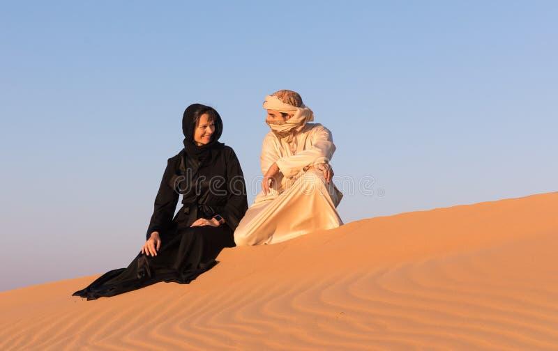 Le coppie si sono vestite in abbigliamento arabo tradizionale in deserto fotografia stock libera da diritti