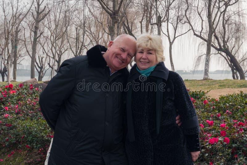 Le coppie sorridenti felici europee adulte in primavera parcheggiano immagini stock libere da diritti