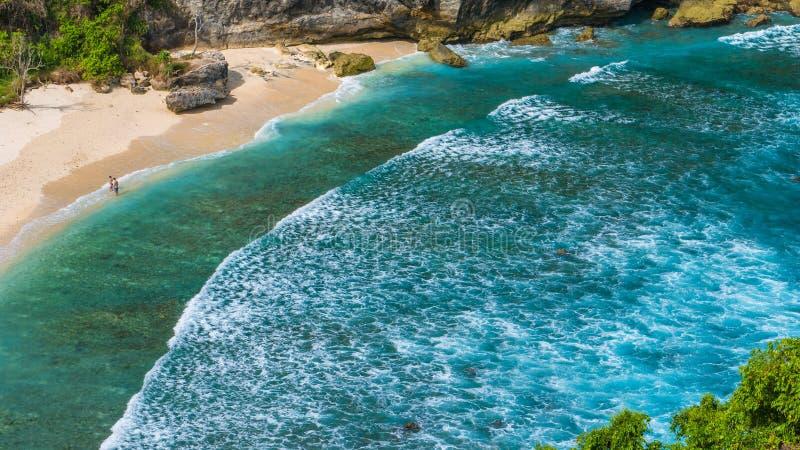 Le coppie su bello Atuh tirano con le onde lunghe bianche, Nusa Penida, Bali, Indonesia fotografie stock