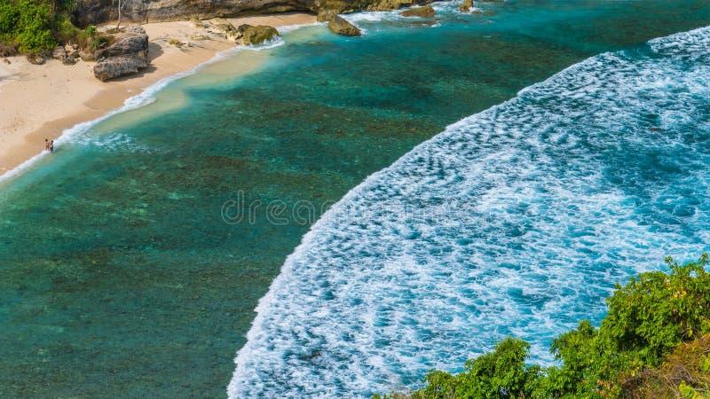 Le coppie su bello Atuh tirano con le onde lunghe bianche, Nusa Penida, Bali, Indonesia fotografie stock libere da diritti
