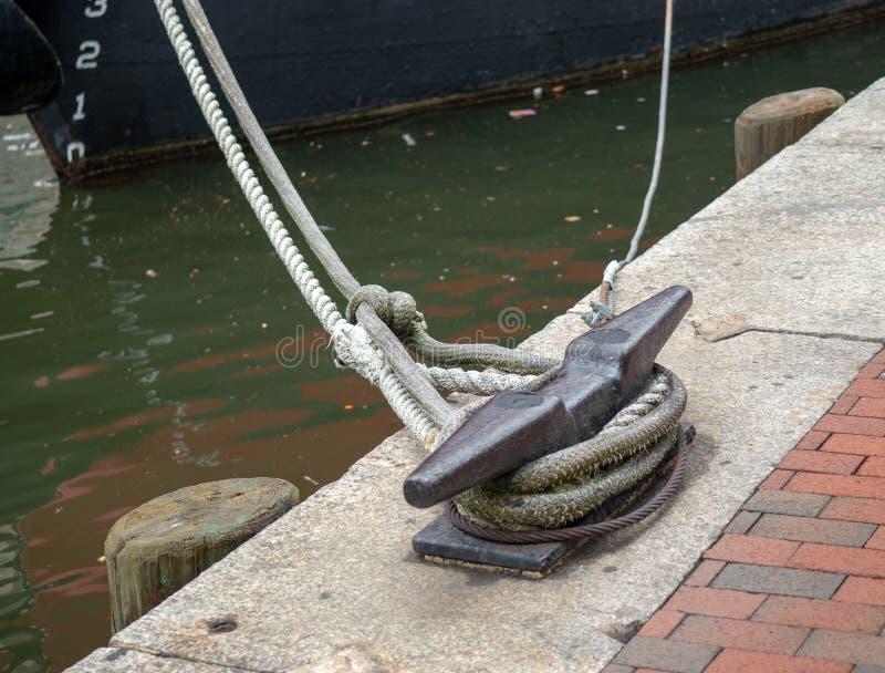 Le corde da una barca legata ad un morsetto si impigliano in un'area sporca del porto fotografia stock libera da diritti