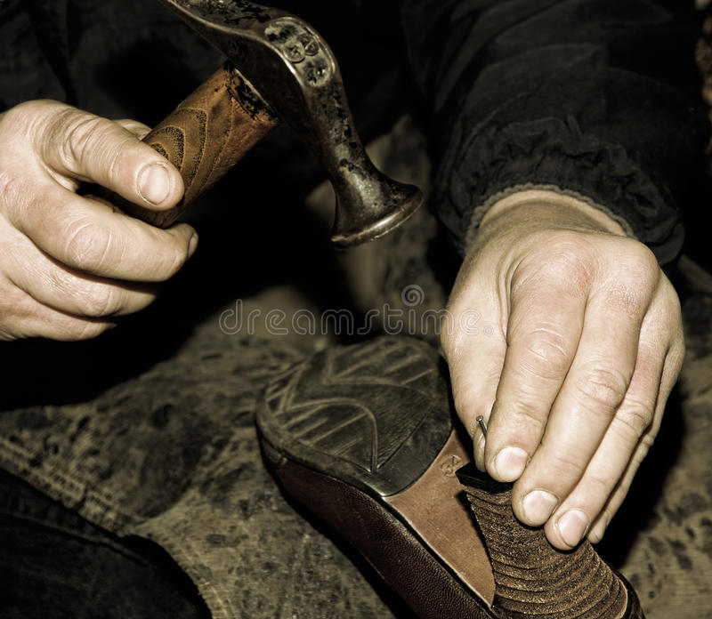 Le cordonnier répare la chaussure le rétro style a modifié la tonalité l'image photo libre de droits