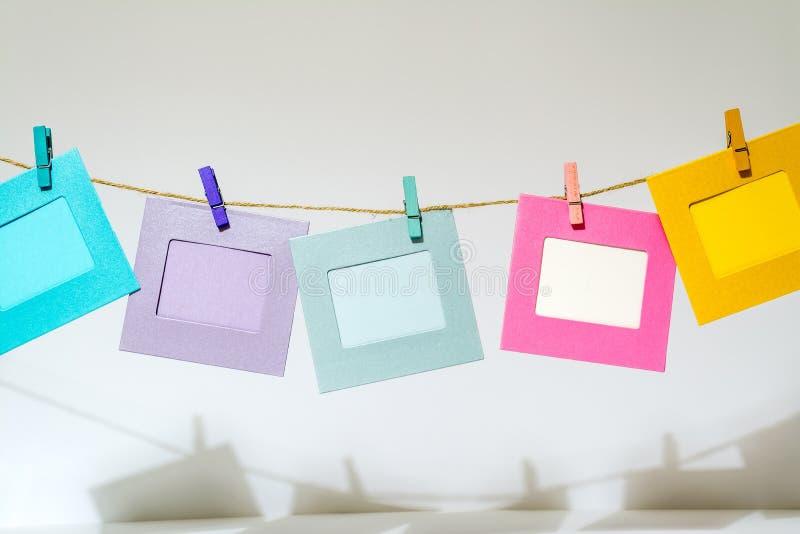 Le cornici divertenti di Colorfu che appendono sulla corda con le mollette da bucato attorcigliano fotografia stock