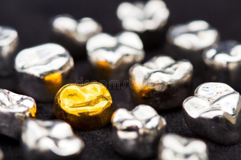 Le corone del dente del metallo e dell'oro dentario sul nero scuro sorgono fotografia stock