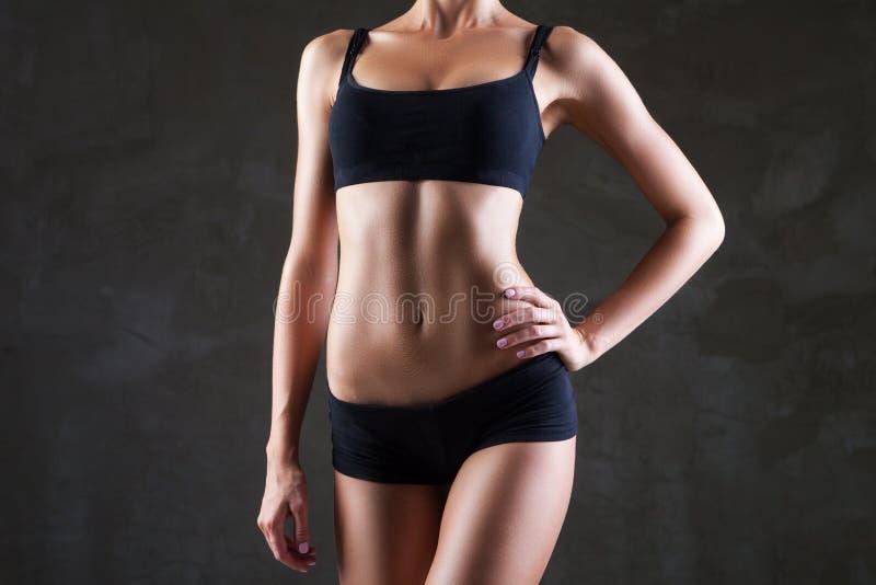 Le corps de la femme mince au-dessus du fond gris-foncé photo stock
