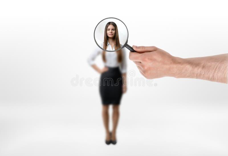 Le corps et le visage unfocused de femme d'affaires se sont focalisés avec la loupe photographie stock