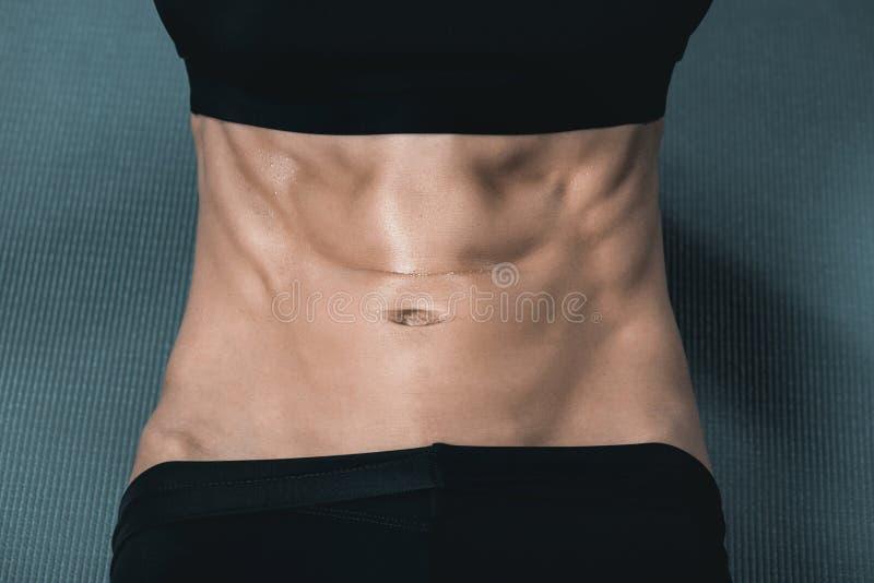 le corps musculaire de la femme avec de l'ABS sur le tapis photos libres de droits