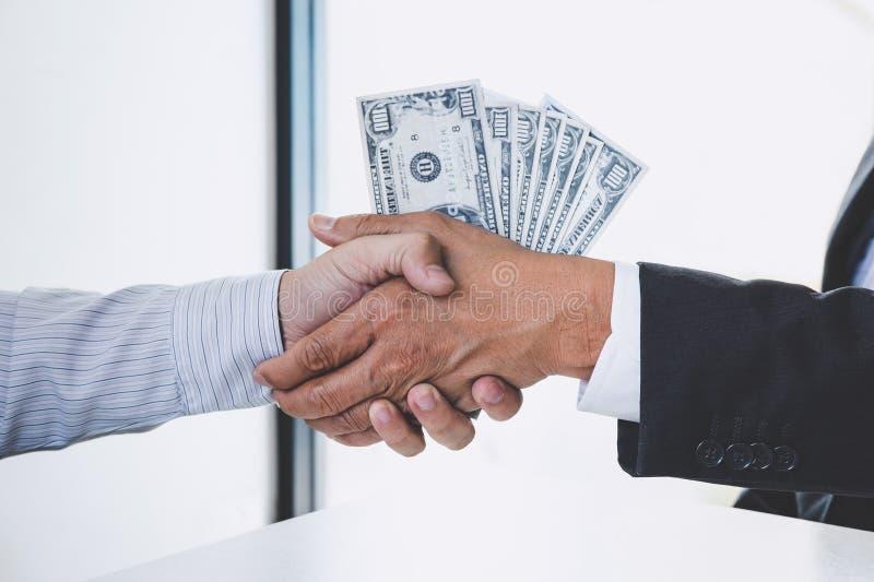 Le corruption et le concept de corruption, paiement illicite sous forme de billets d'un dollar, homme d'affaires se serrant la ma photographie stock libre de droits