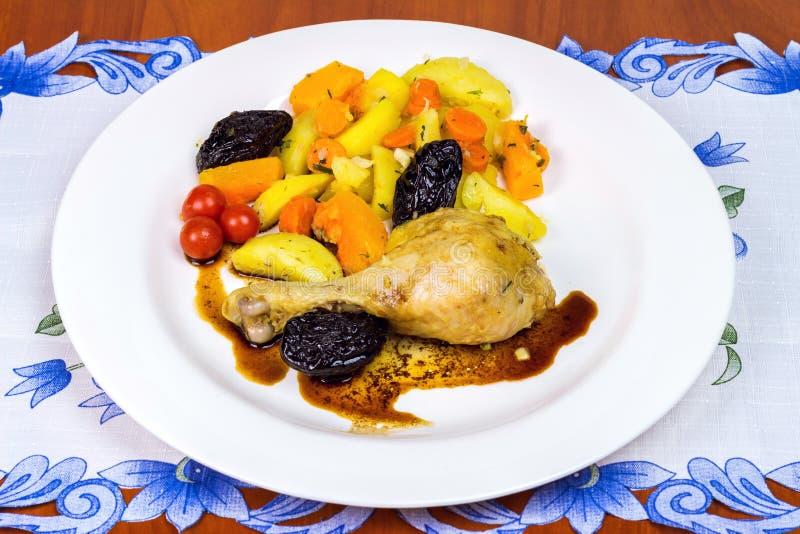 Le coscie di pollo stufate con il pomodoro e la patata sono servito sul piatto bianco immagine stock