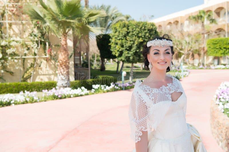 Le cose considerano per nozze all'estero Fondo bianco adorabile della palma di giorno soleggiato del vestito da sposa dalla sposa fotografia stock libera da diritti