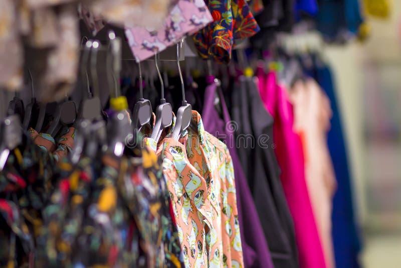 Le cose sono vestiti sui ganci in un deposito d'avanguardia dei vestiti Vestiti su un gancio in un boutique di modo Fuoco seletti immagini stock