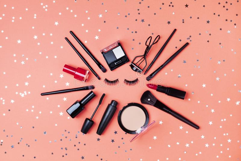 Le cosmétique pour le maquillage de femme et les produits de beauté ont décoré des confettis d'étoile sur la vue supérieure de co image libre de droits