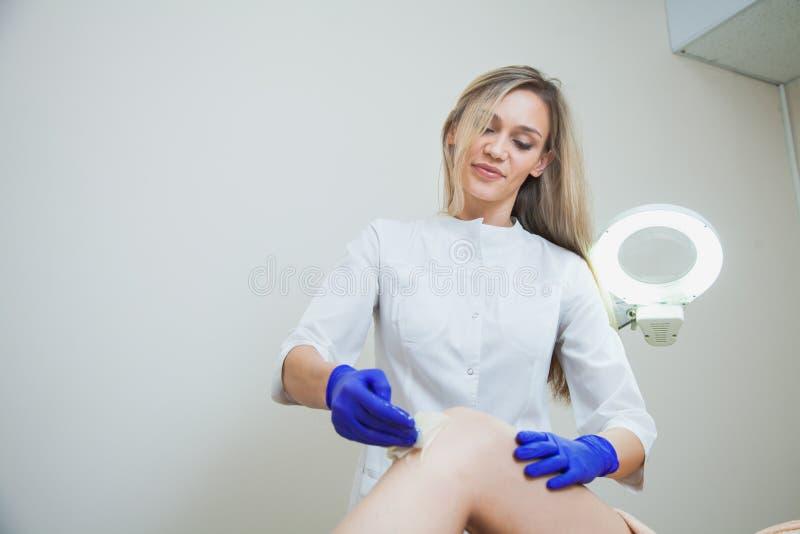 Le cosmetologist d'esthéticien font l'epilation avec la pâte liquide de sucre photo stock