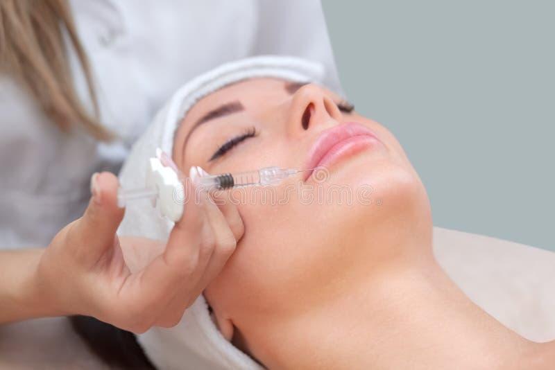 Le cosmetologist de docteur fait la procédure d'injection de Botulinotoxin pour serrer et lisser des rides image libre de droits