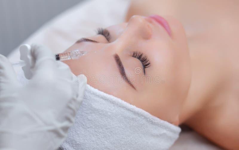 Le cosmetologist de docteur fait la procédure faciale rajeunissante d'injections pour serrer et lisser des rides image libre de droits